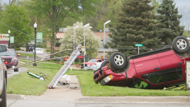 A Ford Explorer rolled over with power lines attached to a snapped light pole entangled around the vehicle on Main Street between Pumpkin Lane and Dexter-Pinckney Road in Pinckney Friday, May 5, 2017.