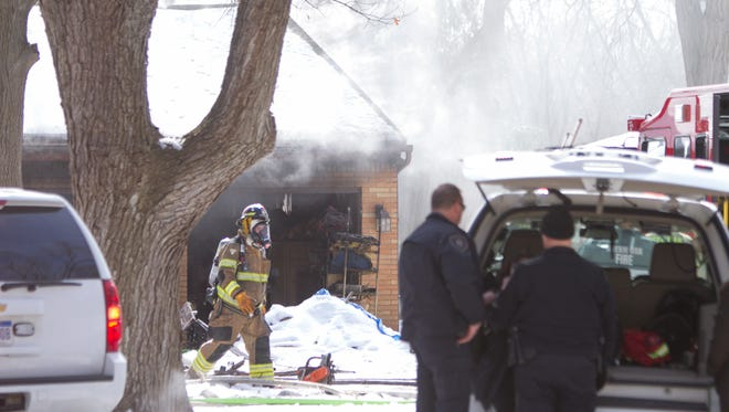 Smoke billows out of an attached garage on a home on Sumpter Dr. in Green Oak Township Monday, Mar. 5, 2018.