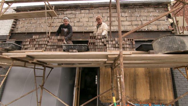 Zander Masonry employee Dan Basnec, left, and owner Davor Zander work on the facade of Mark's Midtown Coney in Howell Wednesday, April 18, 2018.