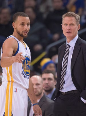 Golden State Warriors head coach Steve Kerr (right) talks to guard Stephen Curry (30) during the first quarter against the Detroit Pistons at Oracle Arena.