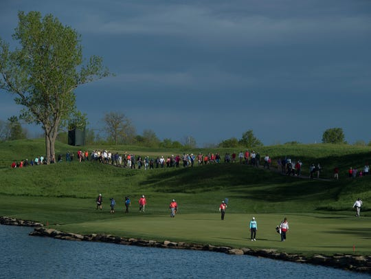 The final group of the day heads down the 18th fairway