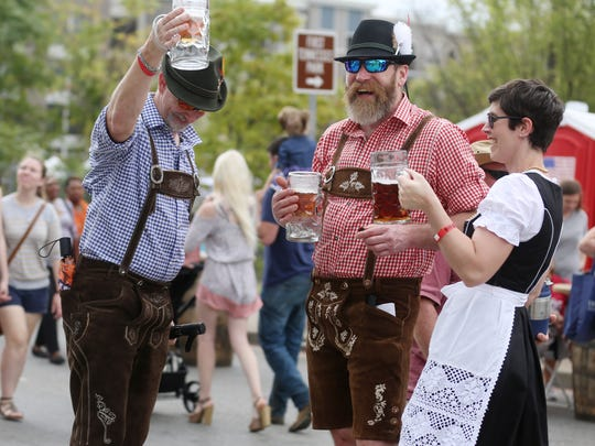 David Gregg, left, Stephen Wilson, center, and Kim Wilson, right, respond to cheers from a passerby during the 2017 Nashville Oktoberfest in Germantown.
