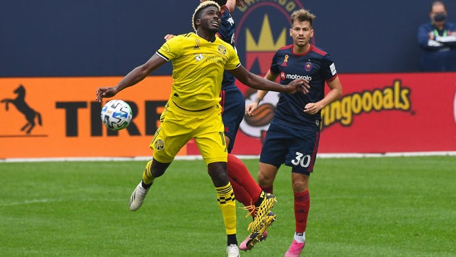 Columbus Crew forward Gyasi Zerdes (11) heads the ball against Chicago Fire midfielder Gaston Gimenez (30) during the first half on Saturday at Soldier Field in Chicago.