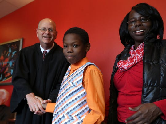 Ja'Maris, 12, stands next to his mother Zyeedah Willis while shaking the hand of Chief Judge Jonathan Sjostrom, who presided over his official adoption on Christmas day at the Big Bend Community Based Care office.
