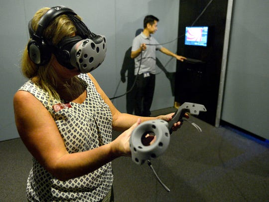 "Debbie Duhadway tries out the Virtual Reality Experience with the help of Carlo Pulido during Thursday's media preview of ""Interactive! The Exhibition"" at the Ronald Reagan Presidential Library & Museum in Simi Valley."