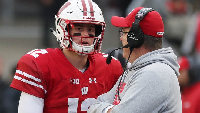 Badgers quarterback Alex Hornibrook talks with coach Paul Chryst. Hornibrook led touchdown drives of 77 and 61 yards.