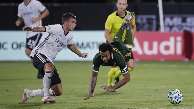 Philadelphia Union defender Kai Wagner, left, and Portland Timbers midfielder Eryk Williamson collide during the first half of Wednesday's match in Lake Buena Vista, Fla.