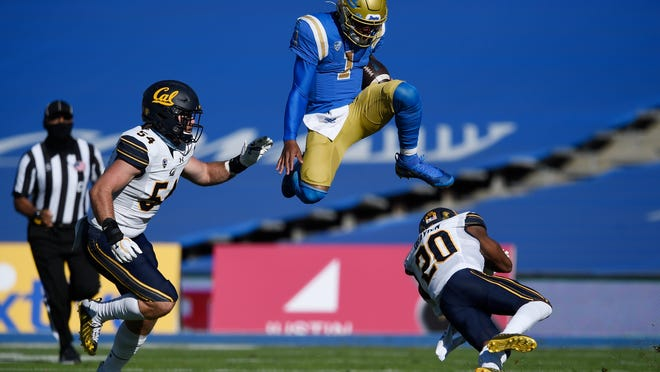 UCLA quarterback Dorian Thompson-Robinson leaps over California's Josh Drayden during the first half of the Bruins' 34-10 win on Sunday at the Rose Bowl.