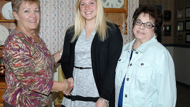 Cassidy Read (center) was honored by the Millville Woman's Club as its Student of the Month for March. She accepts congratulations from Sandy Walter (left), education chairman for the club, and Pam McNamee, club president.