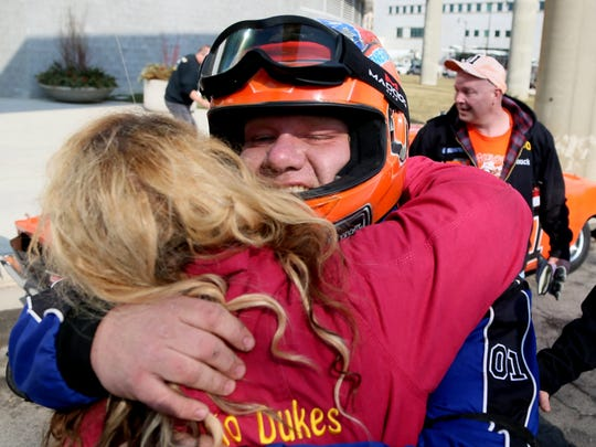 Raymond Kohn, 33 of Warren, Ohio, drove the Charger as part of the Northeast Ohio Dukes Stunt Show, gets a hug from friends after he got out of the 1969 Dodge Charger R/T sports car made famous by the Dukes of Hazzard TV show.