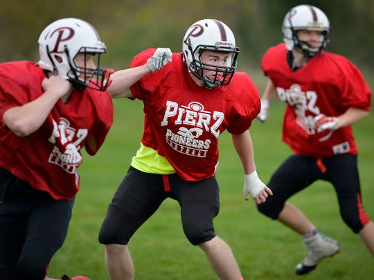 Pierz Pioneers senior running back Derick Hall, center, runs through agility drills with teammates in practice Tuesday at Pierz Healy High School.