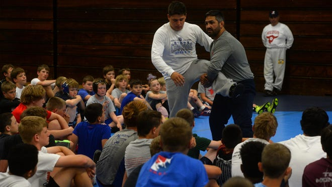Bill Zadick demonstrates a technique for young wrestlers attending the Zadick Brothers Wrestling Camp earlier this summer at Great Falls High.
