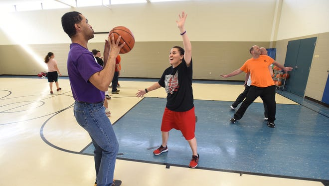 Coach Kasey Bates defends as Eric Schrack prepares to shoot a basket during practice on Tuesday. The Tigers are headed to the Ohio Special Olympics Basketball state semifinals this weekend.
