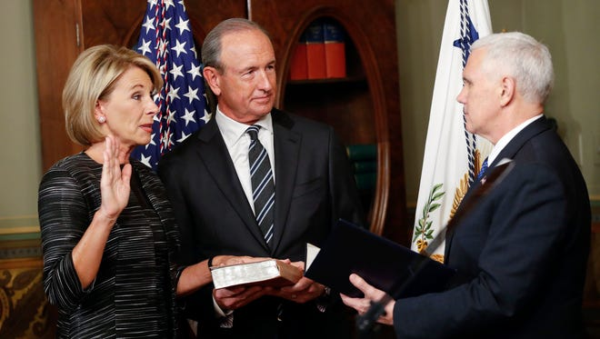 Vice President Mike Pence, right, swears in Education Secretary Betsy DeVos, left, in the Eisenhower Executive Office Building in the White House complex in Washington, Tuesday, Feb. 7, 2017, and are joined buy DeVos' husband Dick DeVos, center.