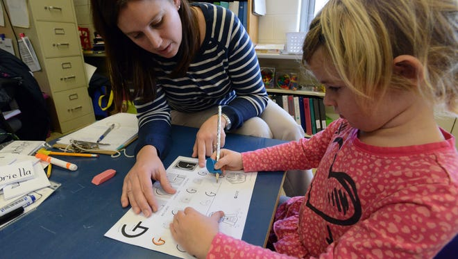 Kristina Binder, left, a Lancaster City Schools preschool teacher, helps Gabby Reed write the letter 'G' Monday afternoon at the former Chief Tarhe Elementary School in Lancaster.