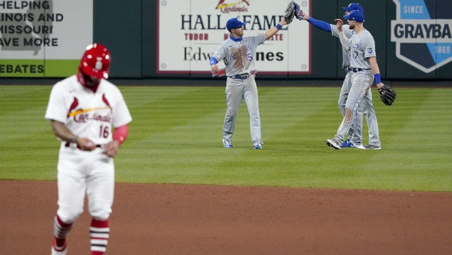 Kansas City Royals' Whit Merrifield (15), Hunter Dozier (17) and Bubba Starling celebrate a 5-4 victory as St. Louis Cardinals' Kolten Wong, left, walks off the field following a baseball game Tuesday, Aug. 25, 2020, in St. Louis.