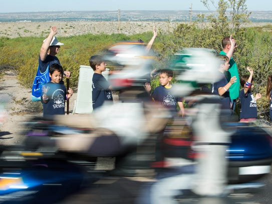 Students from Mission Lutheran School wave at motorcyclists