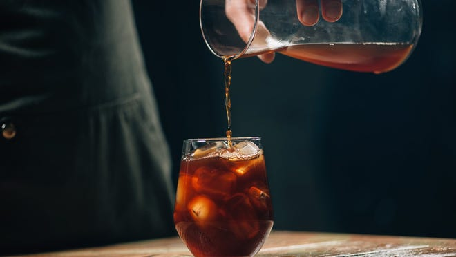Photograph of hand pouring cold coffee into glass of ice
