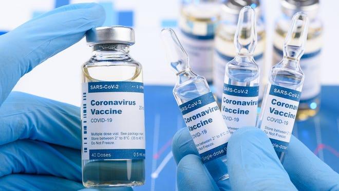 Gloved hands holding coronavirus vaccine vials