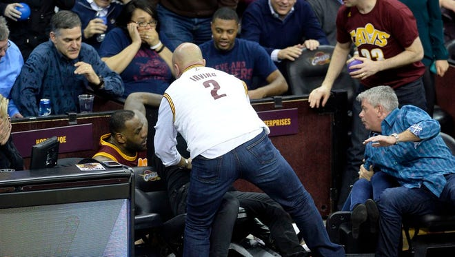 Dec 17, 2015; Cleveland, OH, USA; Cleveland Cavaliers forward LeBron James (23) falls into the court side seats colliding with Ellie Day, wife of golfer Jason Day, in the fourth quarter of a game between the Cleveland Cavaliers and the Oklahoma City Thunder at Quicken Loans Arena. Mandatory Credit: David Richard-USA TODAY Sports