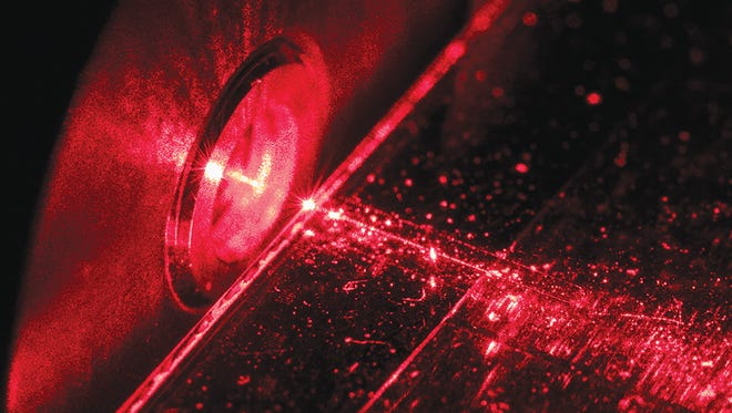 RIT's advanced photonics initiative spans the entire field of photonics from advanced optical systems down to photonics devices the scale of nanometers. Here, the red laser light is directed into a chip with nanoscale photonic devices.