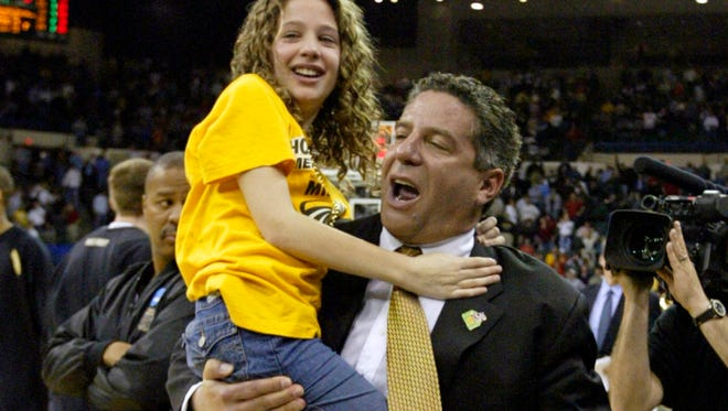 Wisconsin-Milwaukee coach Bruce Pearl carries his daughter, Leah, 11, off the court after beating Boston College, 83-75, in the second round of the NCAA tournament Saturday, March 19, 2005, in Cleveland.