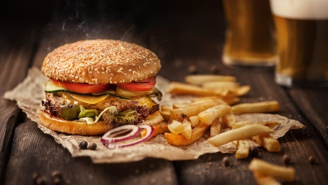 Tasty hamburger with french fries and beer on wooden table