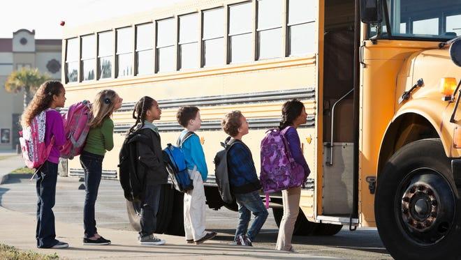 Kids wait to board a school bus.