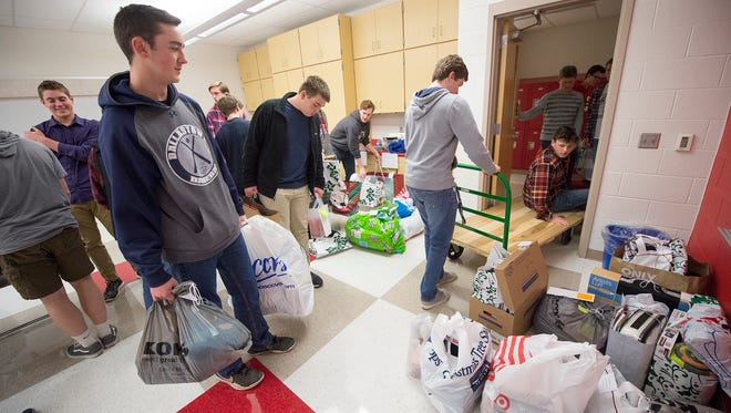 Lee Kling, left, junior Dallastown baseball player works with the team coming and going at a doorway, moving holiday gifts for people in need in the community at the Dallastown Area Middle School.