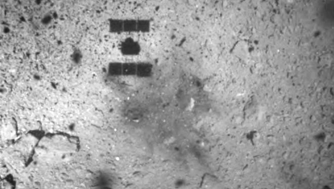 This image released by the Japan Aerospace Exploration Agency shows the shadow, center above, of the Hayabusa2 spacecraft after its successful touchdown on the asteroid Ryugu. Japan's space agency says its Hayabusa2 spacecraft will follow up last month's touchdown on a distant asteroid with another risky mission — to drop an explosive to make a crater and collect underground samples to get possible clues to the origin of the solar system. (JAXA via AP, File)