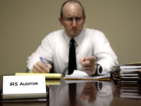 """Man at desk labeled """"IRS Auditor"""" looking a little menacing"""