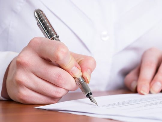 A man signs a piece of paper with a fancy pen.