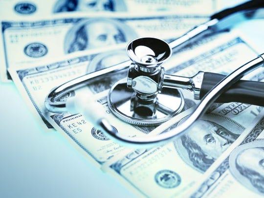 stethoscope sitting on pile of hundred-dollar bills