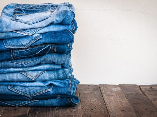 A stack of blue jeans on old wood