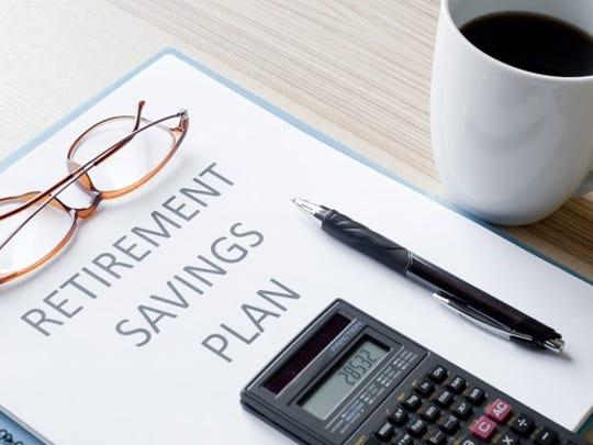 Calculator on top of retirement savings plan binder