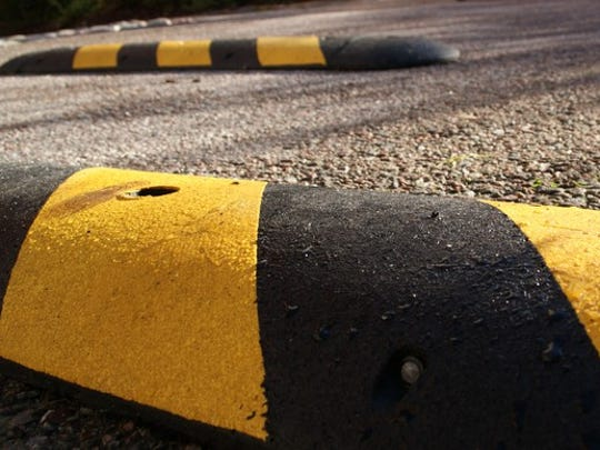 Close-up shot of a black and yellow speed bump with another one in the background.
