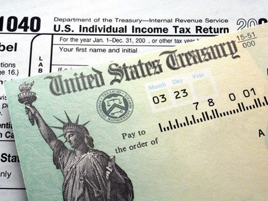 A federal tax refund check lying atop a 1040 tax return.