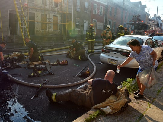 A neighbor, who wished to not be identified, hands out water to firefighters as they rest after battling a blaze in an unoccupied home in the 300 block of S. Penn St. in York City, Sunday, June 11, 2017. John A. Pavoncello photo