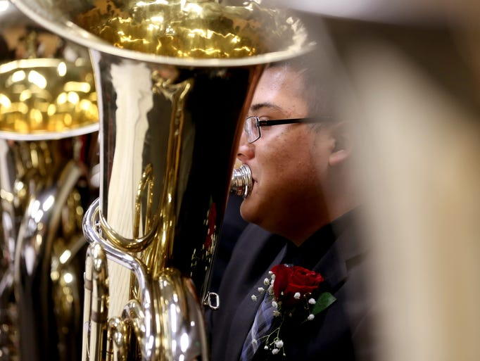 A North Salem High School tuba player warms up before