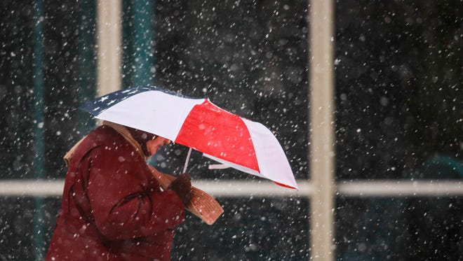 A pedestrian adorned with an American Flag umbrella braves the snow in downtown Louisville. March 4, 2015