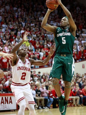 Michigan State guard Cassius Winston (5) shoots the basketball defended by Indiana guard Josh Newkirk in the first half of an NCAA college basketball game, Saturday, Feb. 3, 2018, in Bloomington, Ind.