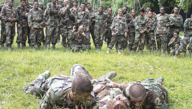 Air Force Junior Reserve Officer Training Corps cadets demonstrate how to properly drag a casualty while under enemy fire during the AFJROTC Chantilly Academy Cadet Leadership Course on Joint Base Andrews Naval Air Facility in Washington on June 25, 2015.