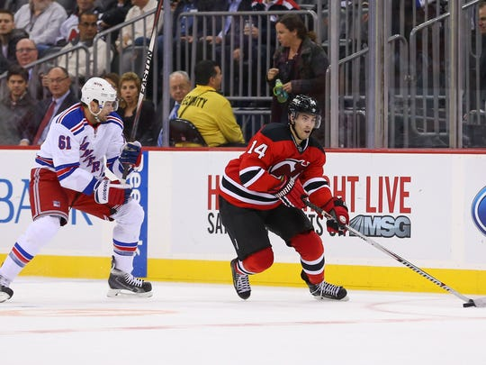 Devils center Adam Henrique (14) skates with the puck past Rangers left wing Rick Nash (61) during the second period.