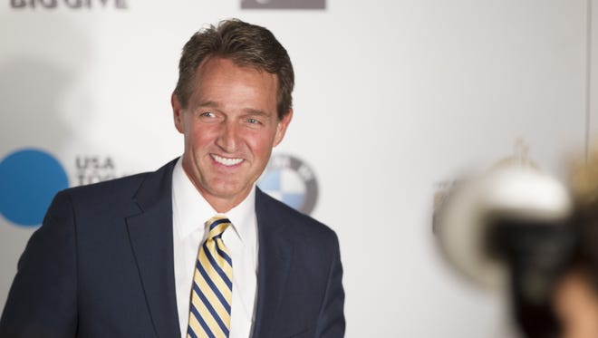 Sen. Jeff Flake poses for pictures before a party at Erika and Matt Williams house in Paradise Valley, AZ on January 31, 2015. The party hopes to raise more than $1 million for a variety of charities, including the Boys and Girls Clubs of Metro Phoenix and the Giving Back Fund