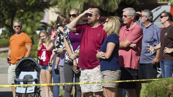 Bystanders look on as emergency personnel work a scene