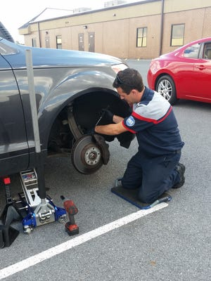 Ryan Boyd of MBM Autho works on a vehicle. The business recently changed its name.