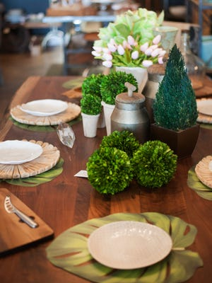 A dining room table is brought to life with green accents at Modern Vintage Home in Cherry Hill. Green is a transcendent color  for home decor.