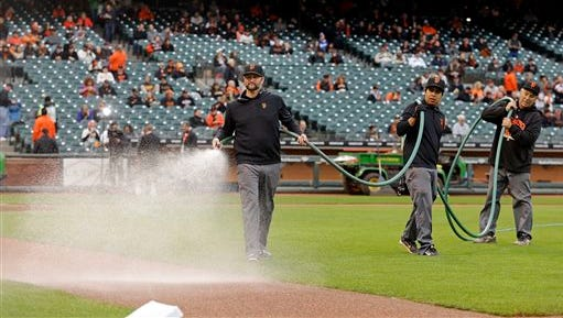 ADVANCE FOR WEEKEND EDITIONS, JUNE 13-14 - In this May 20, 2015 photo, San Francisco Giants lead groundskeeper Greg Elliott, left, waters the infield prior to the baseball game between the Giants and the Los Angeles Dodgers in San Francisco. California's severe drought is affecting how baseball teams operate from Northern California down to San Diego, where the Padres have taken several measures to save. (AP Photo/Ben Margot)