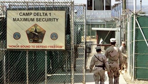 FILE - In this June 27, 2006 file photo, reviewed by a U.S. Department of Defense official, U.S. military guards walk within Camp Delta military-run prison, at the Guantanamo Bay U.S. Naval Base, Cuba. President Barack Obama's declaration that the U.S. is no longer at war in Afghanistan has given rise to new legal challenges from Guantanamo Bay detainees who were captured in that country, but say there's no longer any legal basis to hold them.  (AP Photo/Brennan Linsley, File)