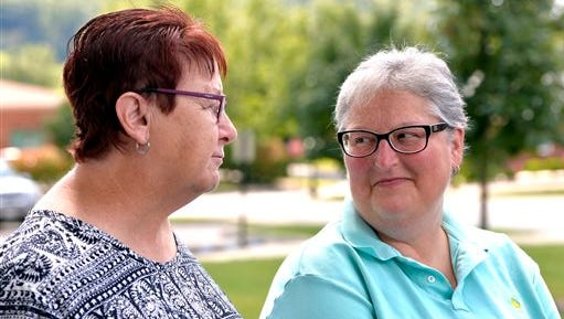 April Miller, right, looks on as her partner Karen Roberts as she addresses the media outside the Rowan County courthouse in Morehead, Ky., Thursday, Aug. 13, 2015. Miller and Roberts, two of the original plaintiffs in the federal suit against Rowan County, Ky., and Rowan County Clerk Kim Davis were at the courthouse to apply for their marriage license following U.S. District Judge David Bunning's decision Wednesday ordering Davis to begin issuing marriage licenses. (AP Photo/Timothy D. Easley)
